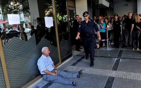 An elderly man is crying outside a national bank brunch as pensioners queue to get their pensions, with a limit of 120 euros, in Thessaloniki on 3 July, 2015. Greece is almost evenly split over a crucial weekend referendum that could decide its financial fate, with a 'Yes' result possibly ahead by a whisker, the latest survey Friday showed. Prime Minister Alexis Tsipras's government is asking Greece's voters to vote 'No' to a technically phrased question asking if they are willing to accept more tough austerity conditions from international creditors in exchange for bailout funds. AFP PHOTO /Sakis MitrolidisSAKIS MITROLIDIS/AFP/Getty Images