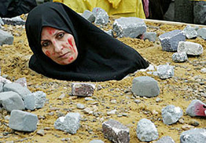 An Iranian woman, symbolically dressed up as a victim of death by stoning, takes part in a protest of the National Council of Resistance of Iran outside a European Union foreign ministers meeting in Brussels November 7, 2005. About 4,000 supporters of the Iranian opposition were protesting as the European Union is studying a call by Iran to resume negotiations over the country's nuclear programme.   REUTERS/Thierry Roge