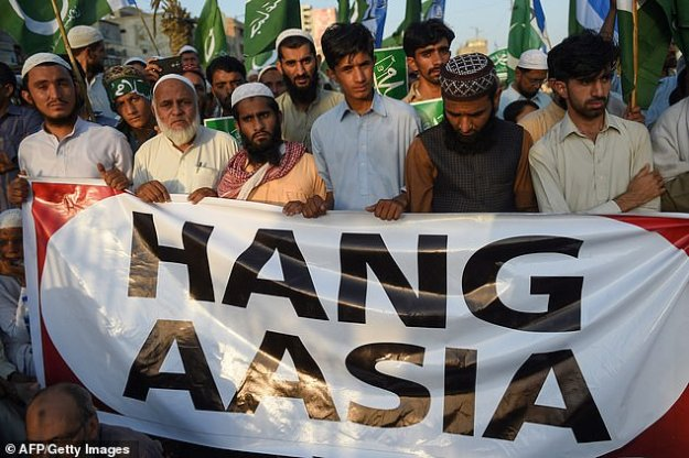 """The sign the Pakistani men are holding should read """"Hang Asia"""""""