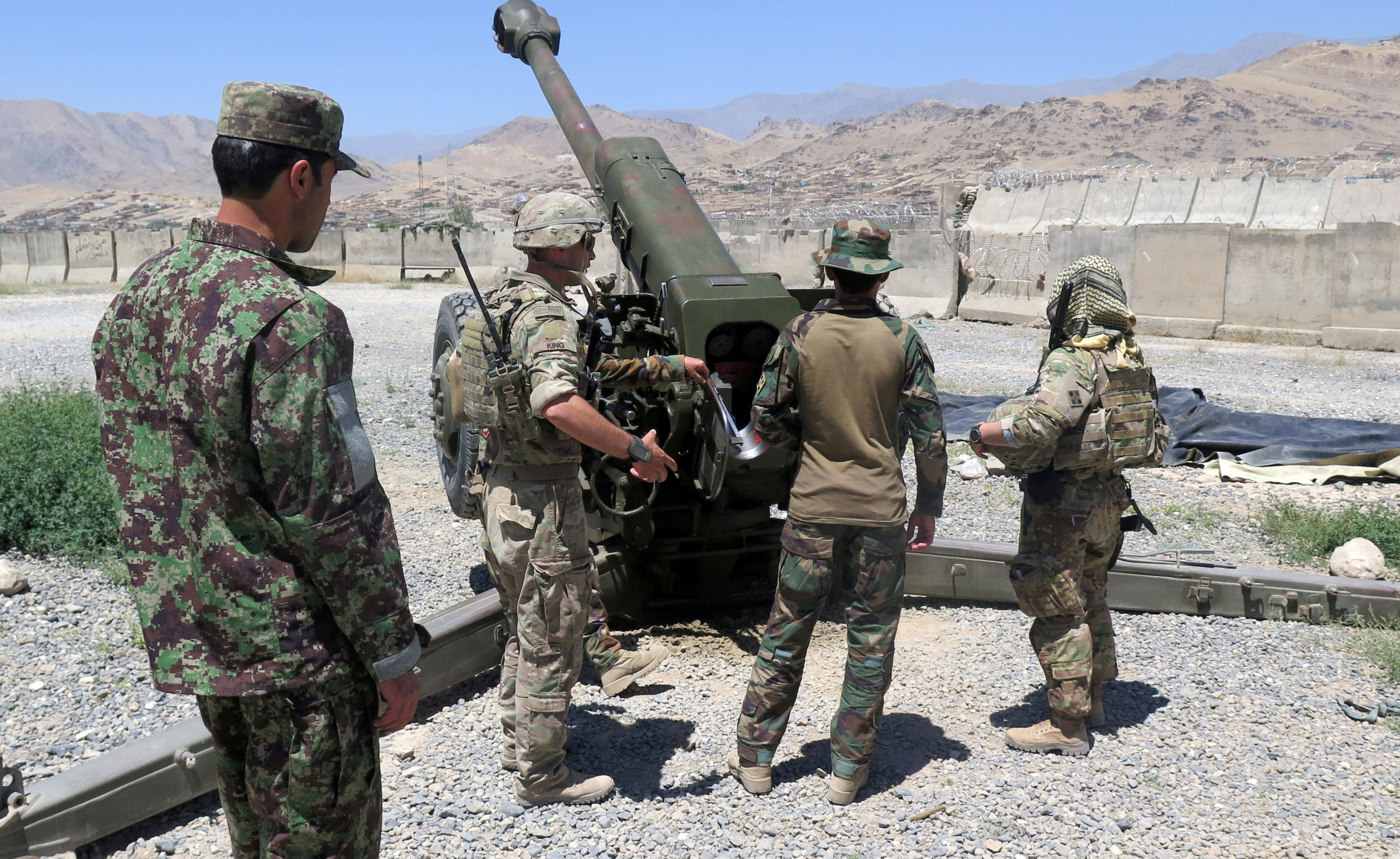 U.S. military advisers from the 1st Security Force Assistance Brigade work with Afghan soldiers at an artillery position on an Afghan National Army base in Maidan Wardak province