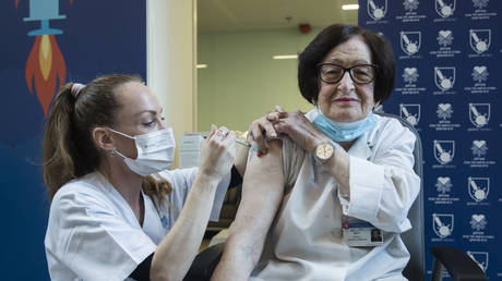 Doctor Verona Radosh, 92, is vaccinated by a medical worker against Coronavirus disease(COVID-19) at Tel Aviv Sourasky Medical Center as Israel starts the COVID 19 vaccination campaign on December 20, 2020 in Tel Aviv, Israel. © Amir Levy/Getty Images