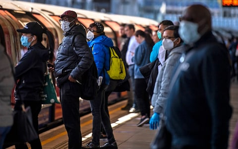 Passengers wear face masks on a platform at Canning Town underground station in London
