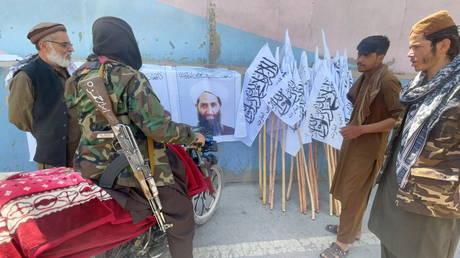 Taliban members stand near a poster of their leader Mullah Haibatullah Akhundzada, in Kabul, Afghanistan, August 26, 2021.