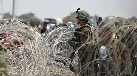 A US soldier stands on guard as Afghans gather on a roadside near the military part of the airport in Kabul on August 20, 2021